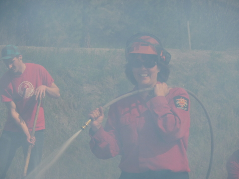 Firestorm female hosing the fire