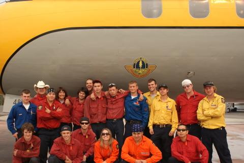 Firestorm Team posing behind airplane